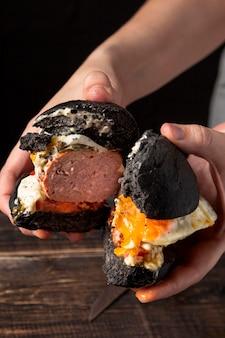 Hoge hoek man met hamburger in tweeën gesneden