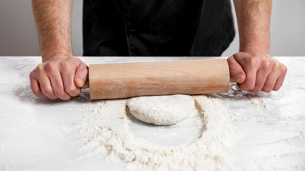 Hoge hoek man rollend pizzadeeg