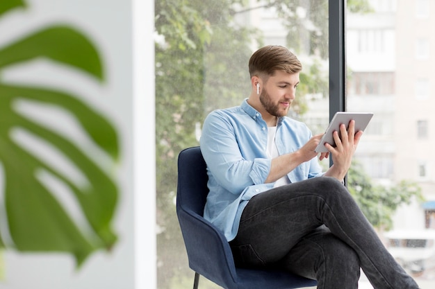 Hoge hoek man zittend op een stoel met tablet