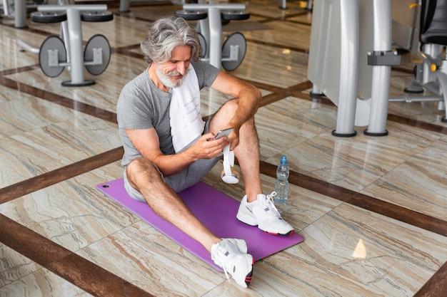 Hoge hoek man zittend op yoga mat