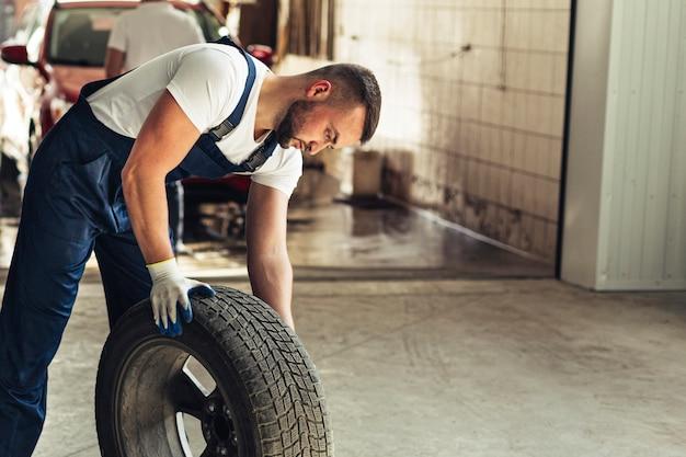 Hoge hoek mannelijke mechanische werknemer bij de autodienst