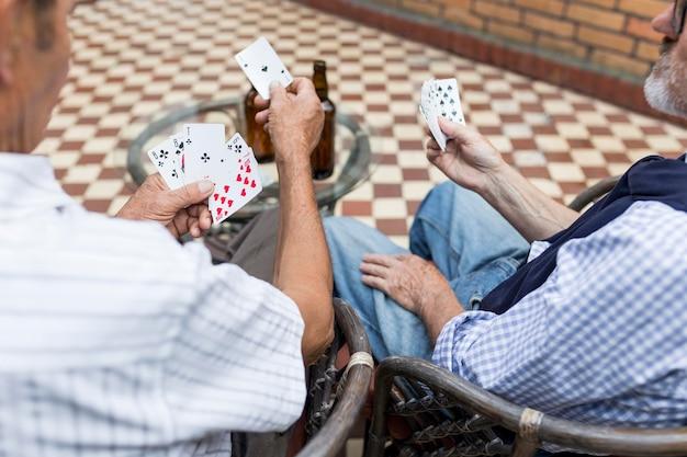 Hoge hoek mannen speelkaarten buitenshuis