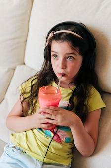 Hoge hoek meisje met koptelefoon sap drinken