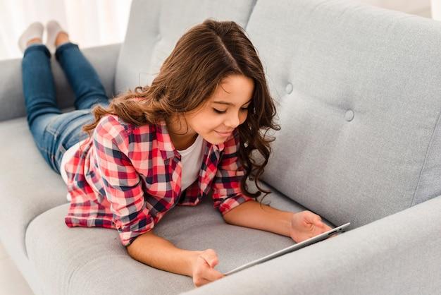 Hoge hoek meisje op bank met behulp van tablet pc