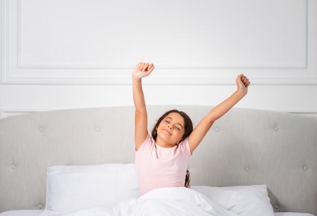 Hoge hoek meisje op bed wakker