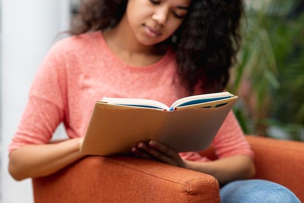 Hoge hoek meisje op leunstoel lezen