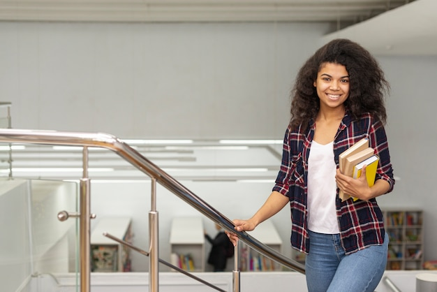 Hoge hoek meisje op trappen met stapel boeken