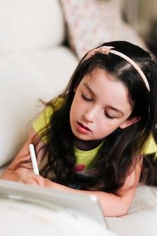 Hoge hoek meisje puttend uit haar tablet