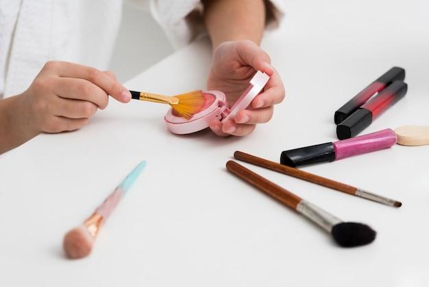 Hoge hoek meisje speelt met haar moeders cosmetica