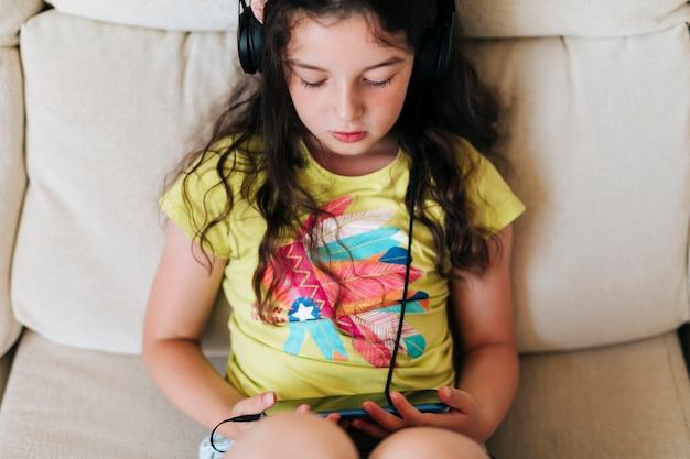 Hoge hoek meisje zitten en kijken naar de telefoon