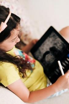 Hoge hoek meisjeszitting op de laag met tablet en pen