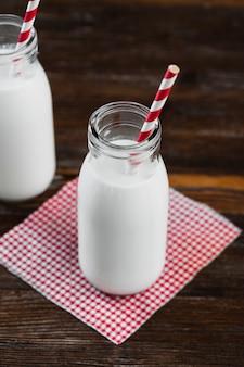 Hoge hoek melkfles met stro op tafel
