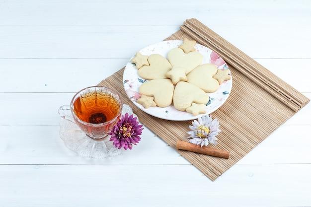 Hoge hoek mening hartvormig en ster cookies, bloemen in placemat met kaneel