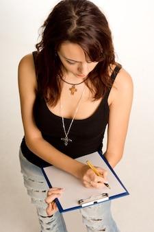 Hoge hoek mening van een jonge vrouwelijke student in casual jeans staande schrijven op een handheld klembord notities maken