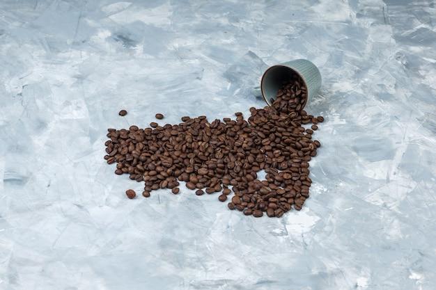 Hoge hoek mening verspreide koffiebonen uit cup op grijze gips achtergrond. horizontaal