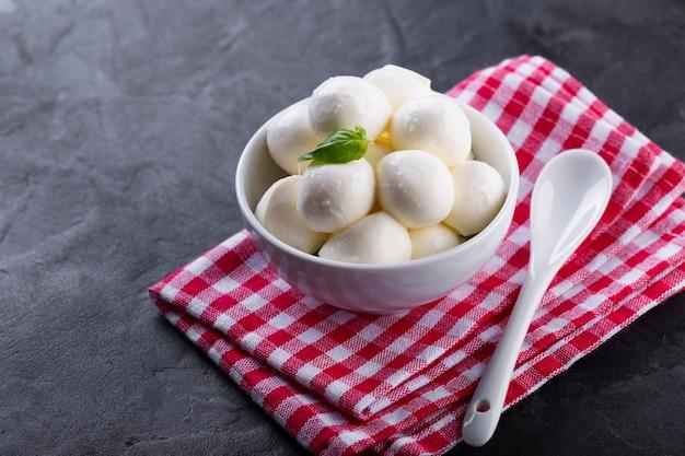 Hoge hoek mini mozzarella in kom met basilicum