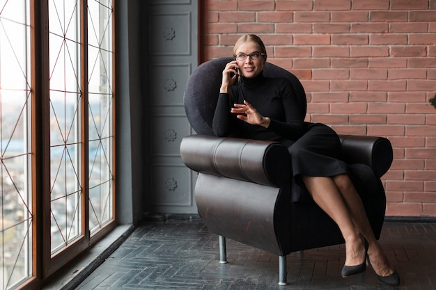 Hoge hoek moderne vrouw die bij mobiel spreekt