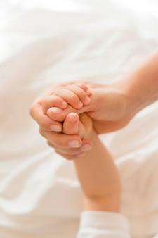 Hoge hoek moeder en baby hand in hand