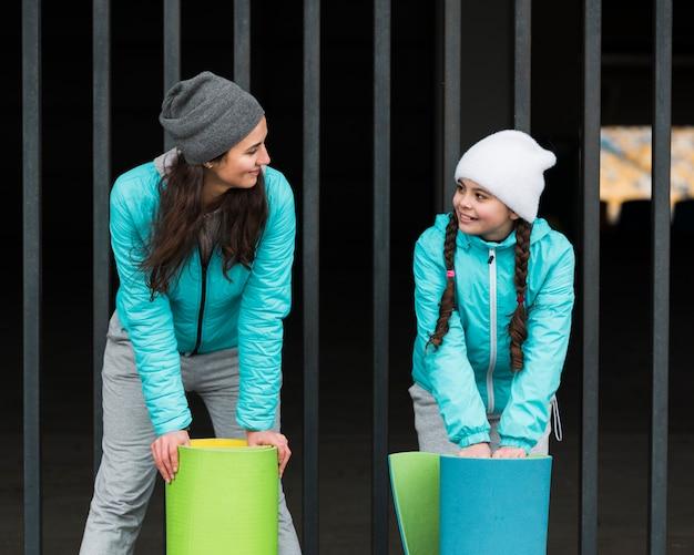 Hoge hoek moeder en meisje met yogamat