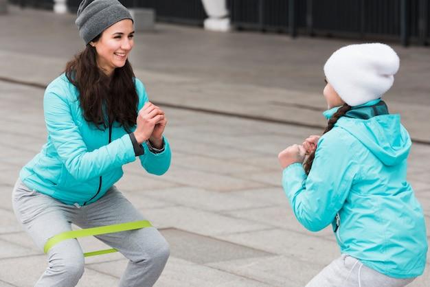 Hoge hoek moeder en meisje training met elastische band