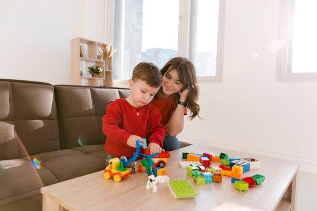 Hoge hoek moeder en zoon spelen met speelgoed