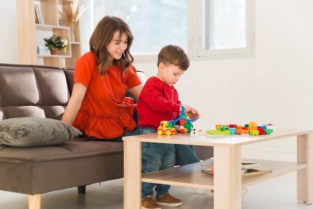 Hoge hoek moeder kijken zoon tijdens het spelen