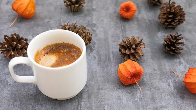 Hoge hoek mok met koffie en dennenappels