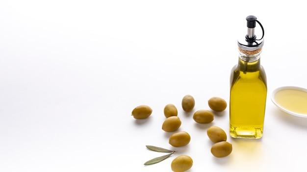 Hoge hoek olijfolie fles met gele olijven en kopie ruimte