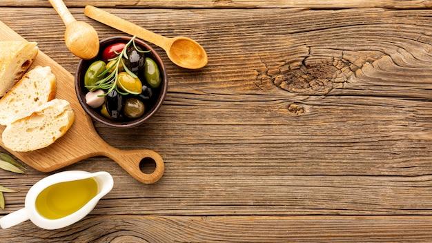 Hoge hoek olijven mix brood en olie flessen met kopie ruimte