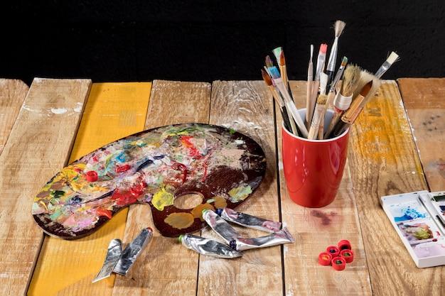Hoge hoek op penselen op mok met palet