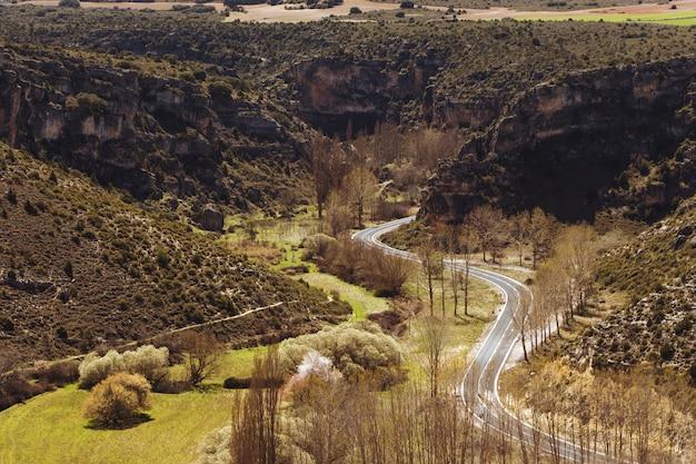 Hoge hoek opname van een bochtige weg omgeven door rotswanden en prachtig groen