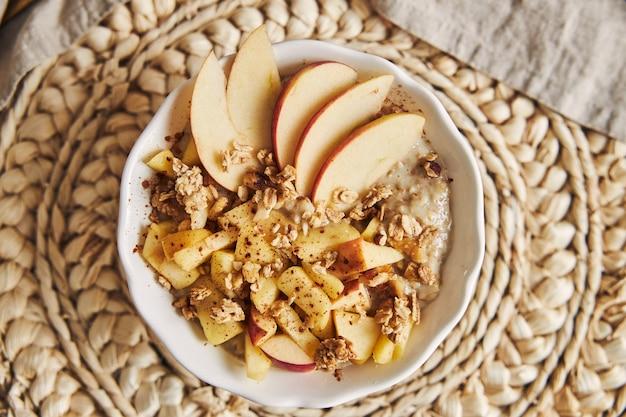 Hoge hoek opname van een kom pap met granen en noten, en plakjes appel op een houten tafel