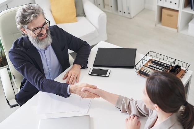 Hoge hoek opname van man en vrouw die aan een bureau voor elkaar zitten en elkaar de hand schudden na een sollicitatiegesprek