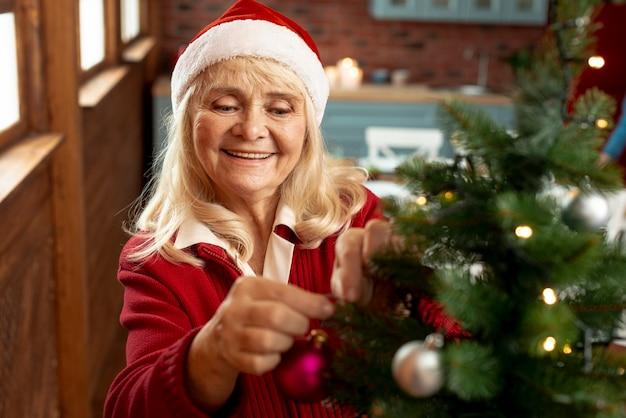Hoge hoek oude vrouw die de kerstmisboom verfraait