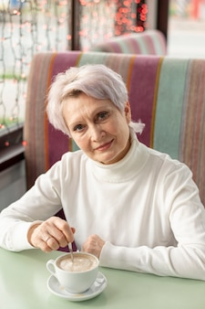 Hoge hoek oudere vrouw die van kop van koffie geniet