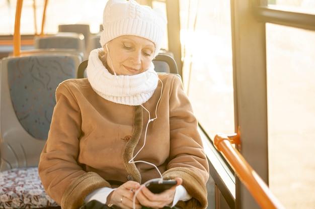 Hoge hoek oudere vrouw in bus het luisteren muziek
