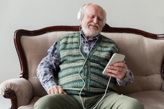 Hoge hoek ouderling op bank die muziek op mobiel speelt