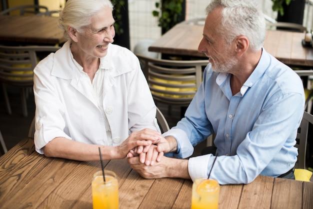 Hoge hoek paar hand in hand bij restaurant