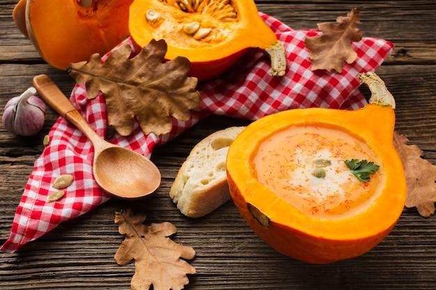 Hoge hoek pompoen bisque en houten lepel met ingrediënten en bladeren