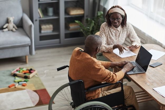 Hoge hoek portret van afro-amerikaanse man met behulp van rolstoel thuiswerken met vrouw, kopieer ruimte