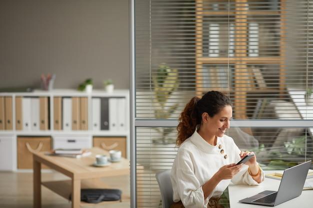 Hoge hoek portret van elegante succesvolle zakenvrouw met behulp van smartphone en glimlachen terwijl u geniet van werk vanuit huis, kopieer ruimte