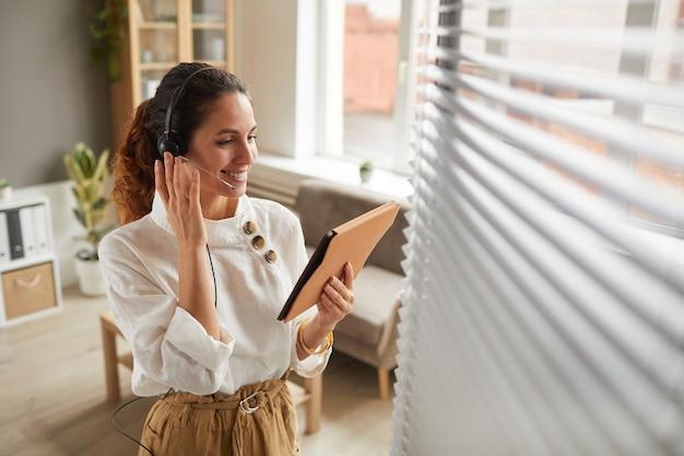 Hoge hoek portret van glimlachende zakenvrouw hoofdtelefoon dragen en digitale tablet te houden tijdens de onlinevergadering in kantoor, kopieer ruimte