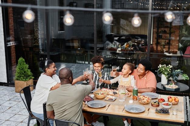 Hoge hoek portret van grote afro-amerikaanse familie rammelende bril terwijl u geniet van het diner samen of...