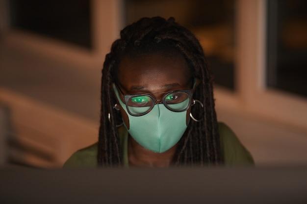 Hoge hoek portret van hedendaagse afro-amerikaanse vrouw masker dragen tijdens het gebruik van computer verlicht door scherm in donkere kantoor, kopieer ruimte