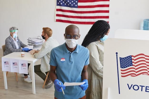 Hoge hoek portret van jonge afro-amerikaanse kiezer dragen masker staande door stand en op post-pandemische verkiezingsdag, kopie ruimte