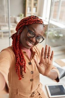 Hoge hoek portret van jonge afro-amerikaanse vrouw zwaaien naar de camera tijdens het nemen van selfie foto of live streaming vanuit kantoor aan huis