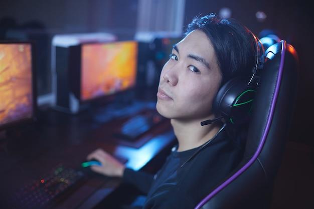 Hoge hoek portret van jonge aziatische man spelen van videospellen in cybersport stoel, kopie ruimte