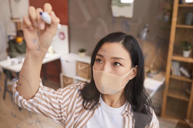 Hoge hoek portret van jonge aziatische zakenvrouw schrijven op glazen paneel tijdens de planning van project in kantoor, kopieer ruimte