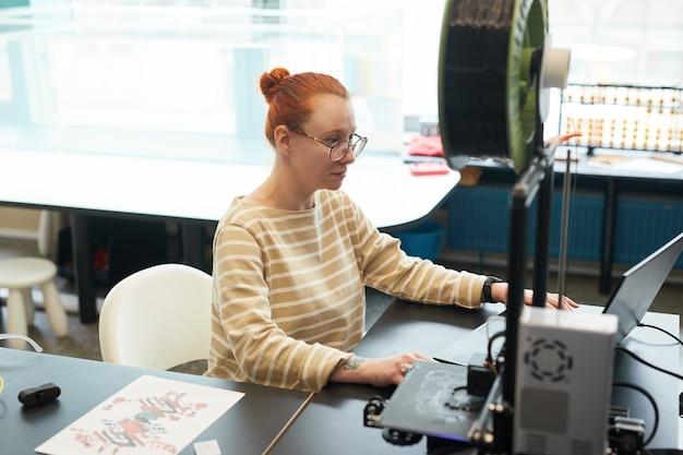 Hoge hoek portret van jonge roodharige vrouw met behulp van 3d-printer tijdens engineering klasse op de universiteit, kopieer ruimte