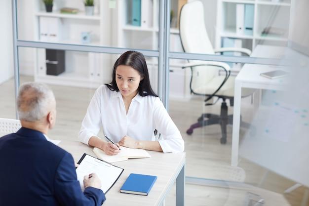 Hoge hoek portret van jonge vrouw beantwoorden van vragen tijdens sollicitatiegesprek in kantoor